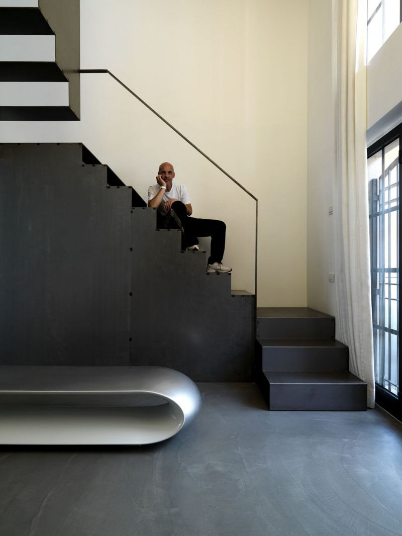 This large black staircase was designed with cut outs at the back of each step to allow light to pass through and help brighten the space while still maintaining an industrial look.