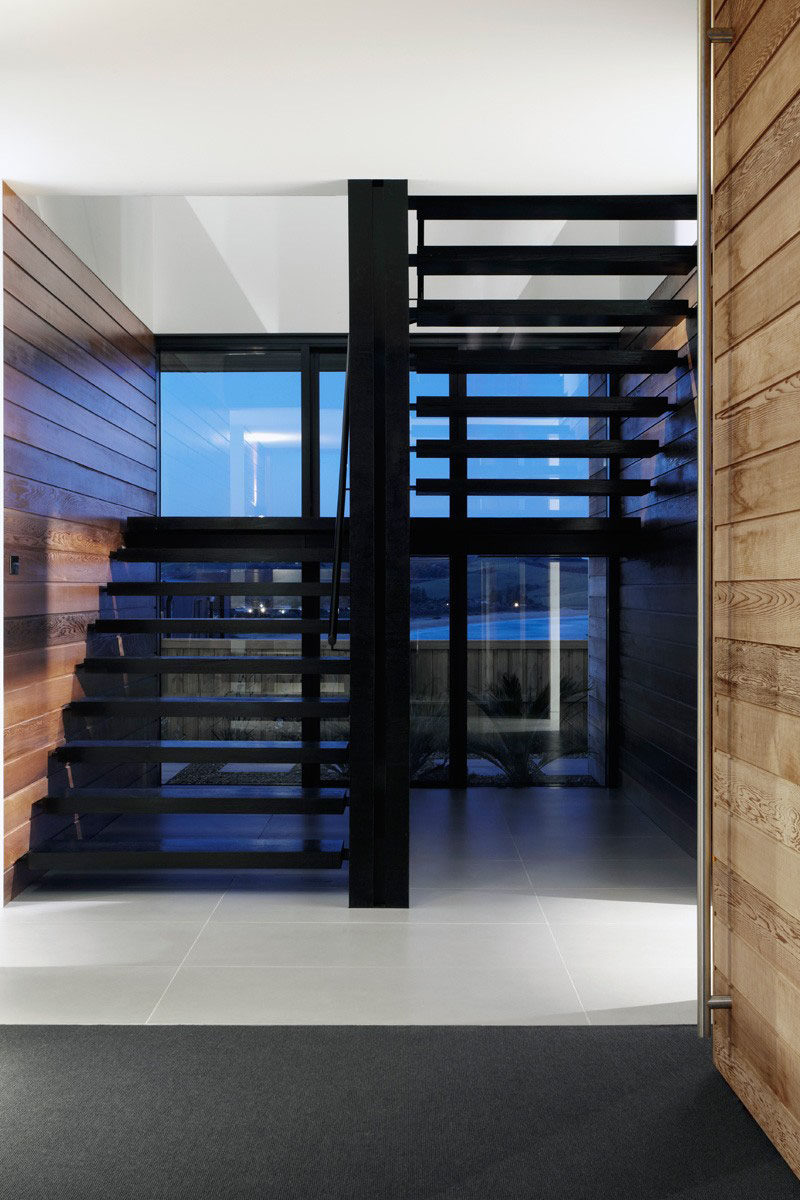 The openings between each step on these black stairs keep the entryway bright and let you take in the views as soon as you step in the door.