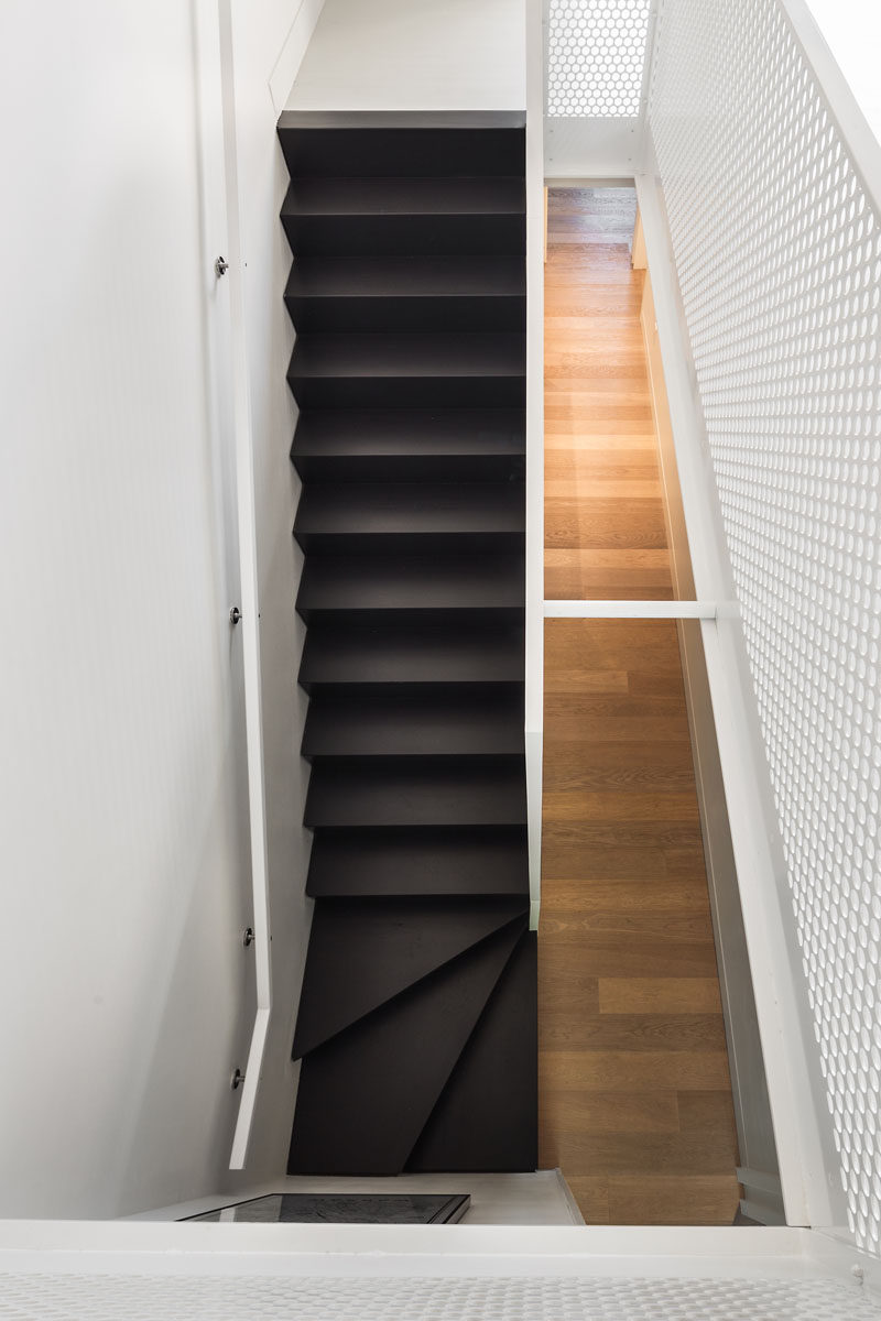 These black modern stairs are surrounded by white walls and handrails, as well as light wood flooring making it stand out and become a focal point in the interior.