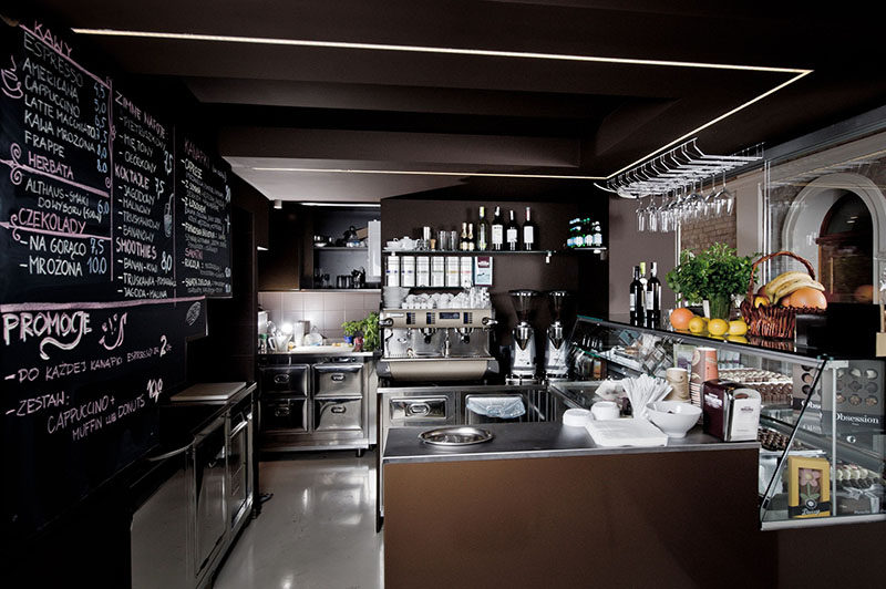 The service area in this modern chocolate shop and cafe is tucked beside a set of stairs and underneath a mezzanine level.