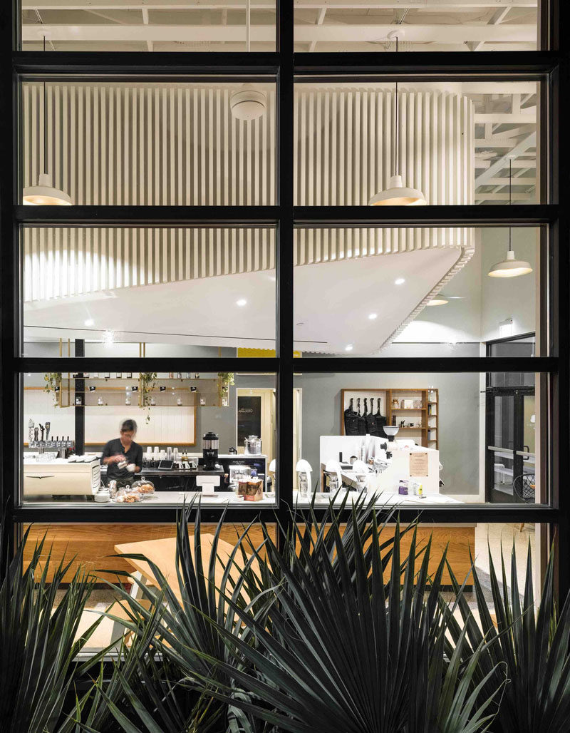 This modern coffee shop has dramatic black framed windows and a bright white interior.
