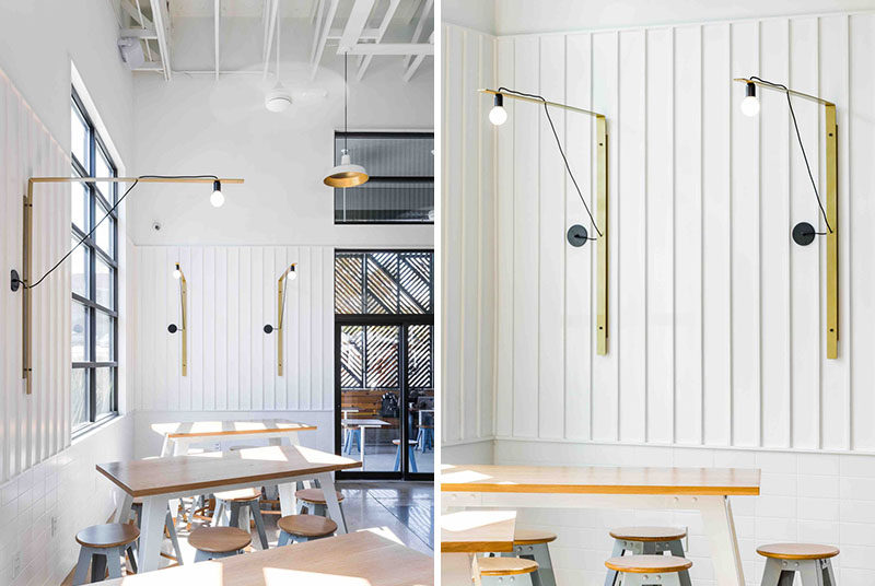 In this modern coffee shop, bar height tables and stools are positioned by the window, with simple metallic gold light fixtures adorning the walls.