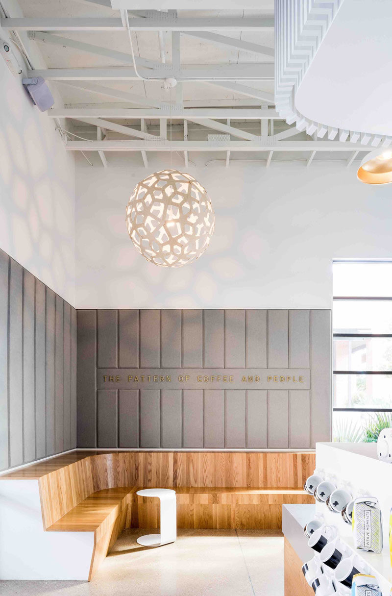 This modern coffee shop has built-in wooden banquette that curves around the corner to create plenty of seating.