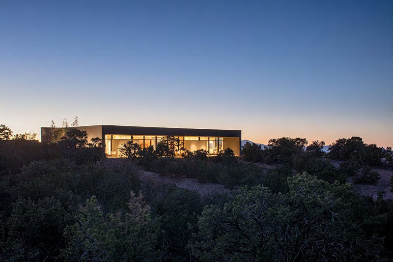 Specht Architects have recently completed this modern home in Santa Fe, New Mexico, that's organised around two perpendicular board-formed concrete walls.