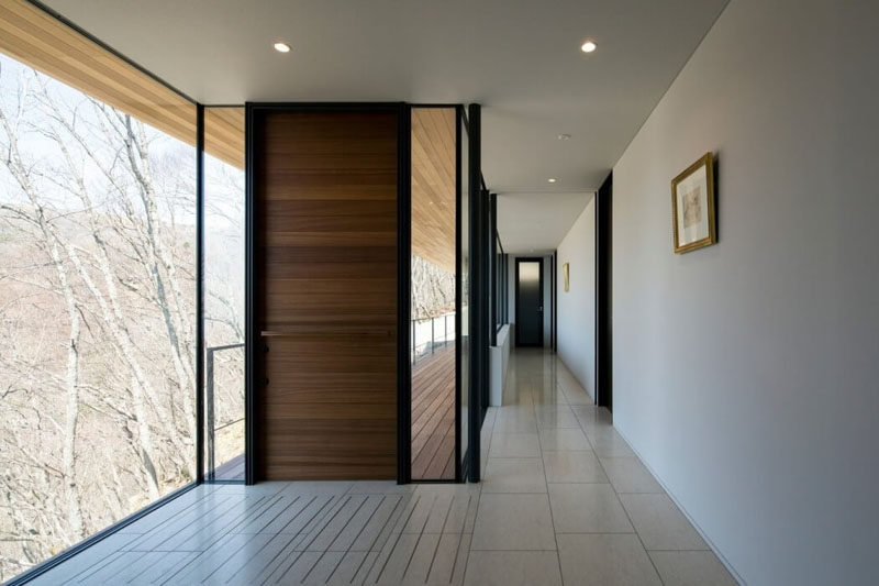 This modern front door with a horizontal wood pattern is surrounded by windows that look out at the trees surrounding the home.