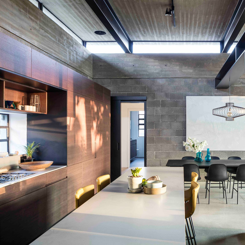 Behind the dining area and the living area in this modern house, is the kitchen. Wood cabinets without hardware keep the kitchen modern and streamlined, while the kitchen island with seating provides a more casual place to dine or help with meal prep.