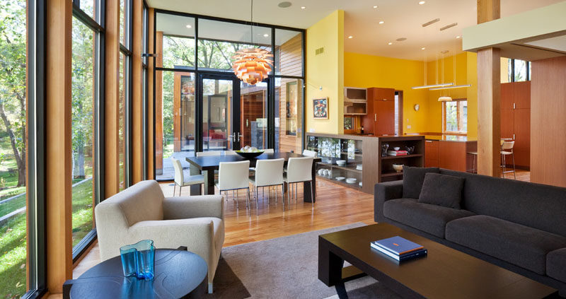 Just off the kitchen in this modern house sits the dining room and living room. Beside the dining room are large glass doors that open up to the outdoors.