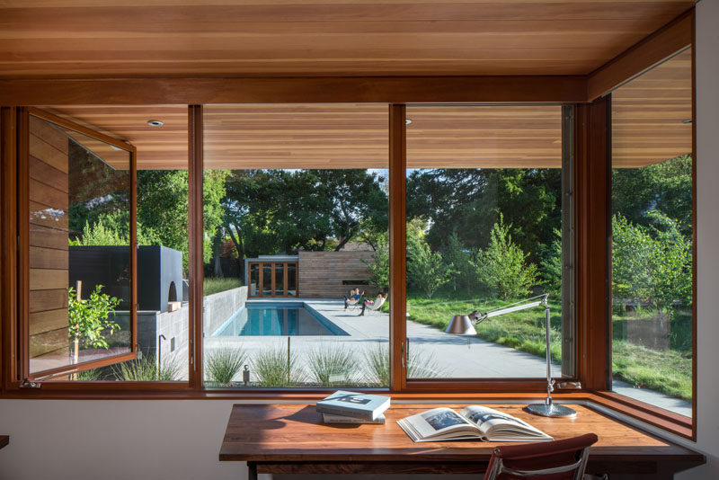 Every room in this modern house, like the home office, has views of the fully landscaped garden. There's a meadow with long grass, a contemplation garden, a swimming pool with patio, and an outdoor kitchen that sits alongside a board-formed concrete garden wall. At the end of the pool is a small guest house with a bedroom, living room and bathroom.
