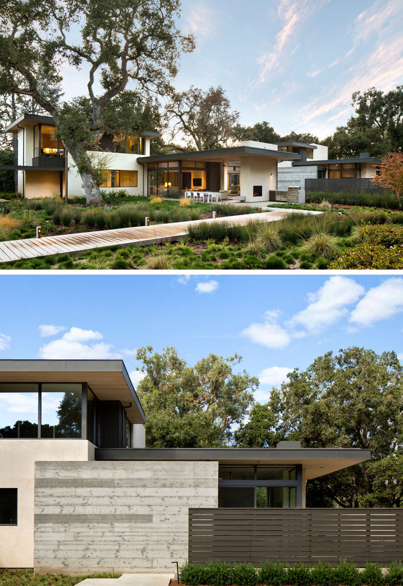 In the backyard of this modern house, the yard has been landscaped to preserve the existing trees and foliage, and has extra greenery added to make the yard more inviting. The concrete, steel, and wood, also visible at the back of the home, contrasts the natural landscape and makes the house stand out with it's modern appearance.