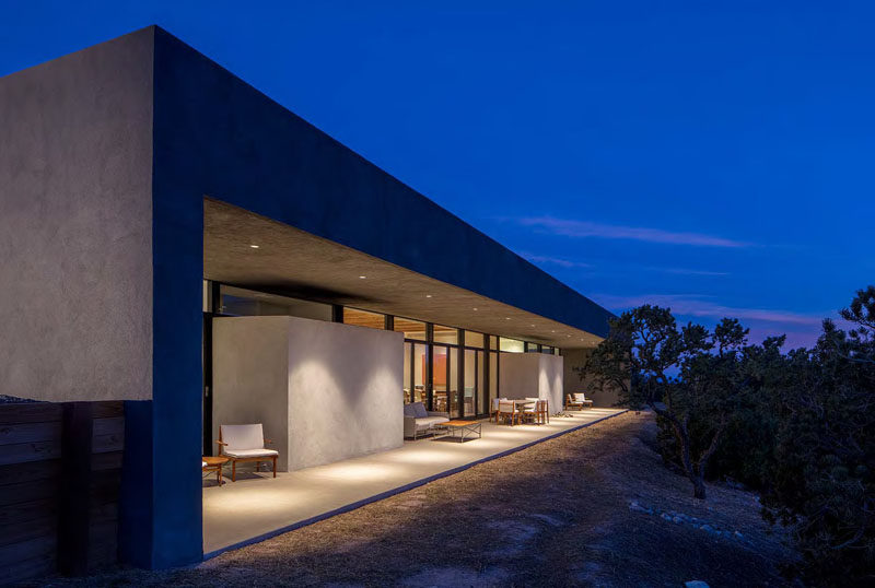 Outside the rear of this modern house is a porch that runs the length of the house. The outdoor porches are shaded by a cantilevered roof, provide a space to relax out of the sun.