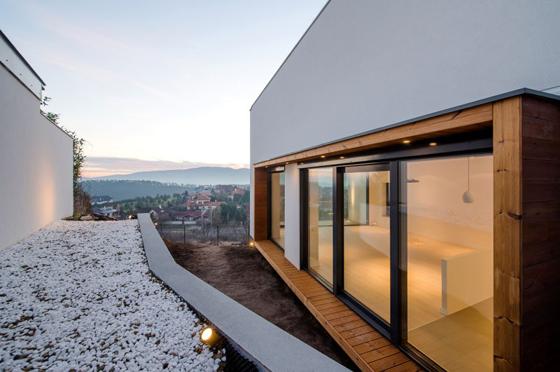 On the side of this modern house, a wood frame surrounds the windows and breaks up the all white exterior walls.