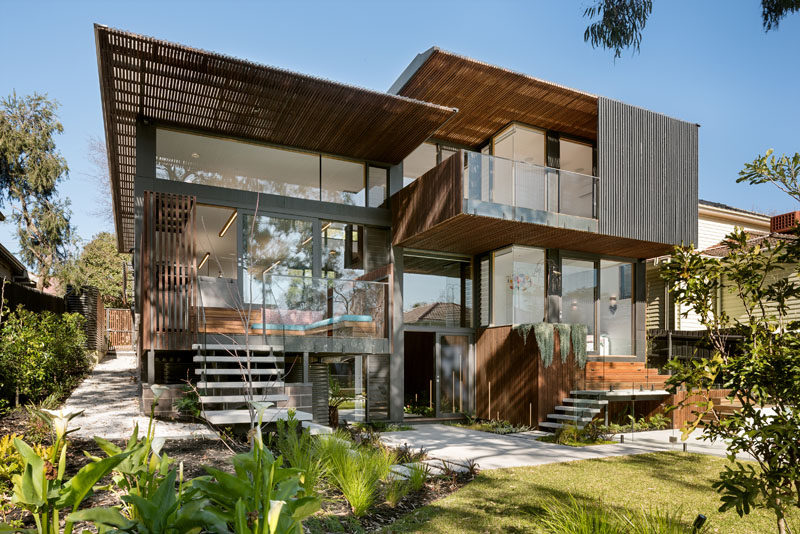 This multi-level modern house has large windows covering much of the back exterior, while steel and wood cover any non-glass surface.