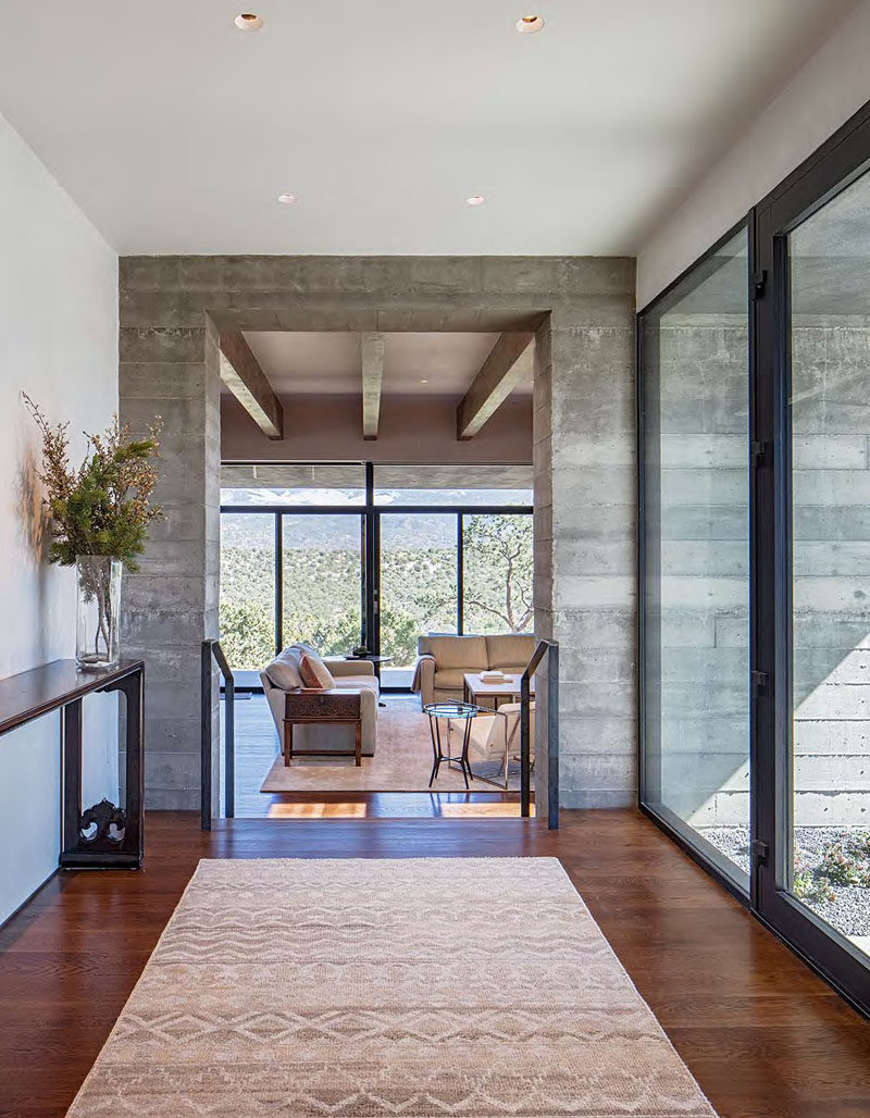 Stepping inside this modern house, there's a foyer with large windows that leads to the living room. From this angle, you can see part of a board-formed concrete wall.