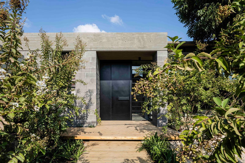 This modern house has a light wood path leading to a black steel front door, that's surrounded by concrete blocks and a concrete roof.