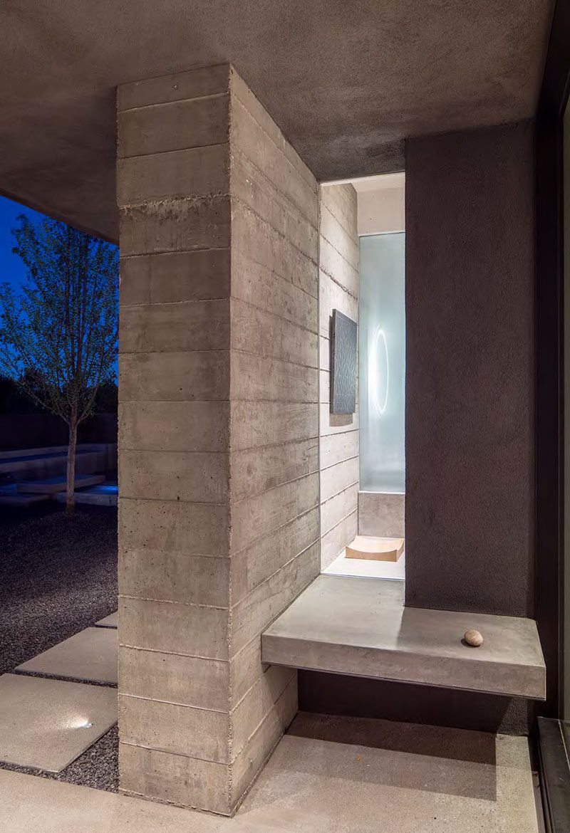 Just before walking through the front door of this modern house, there's a small built-in concrete bench with a window that gives a glimpse of the interior.