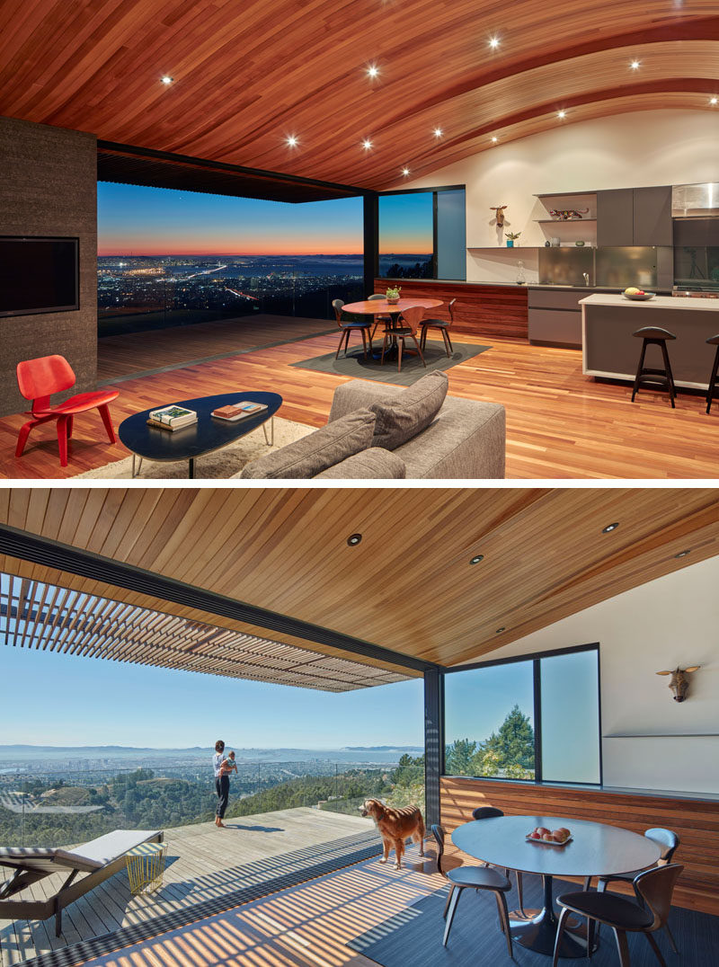 Inside this modern house, an unexpected feature of the interior is the wood ceiling that has curves that echo the contours of the hillside that the house sits on. The main floor which is home to the kitchen, dining room and living room, opens up to a balcony with glass railings.