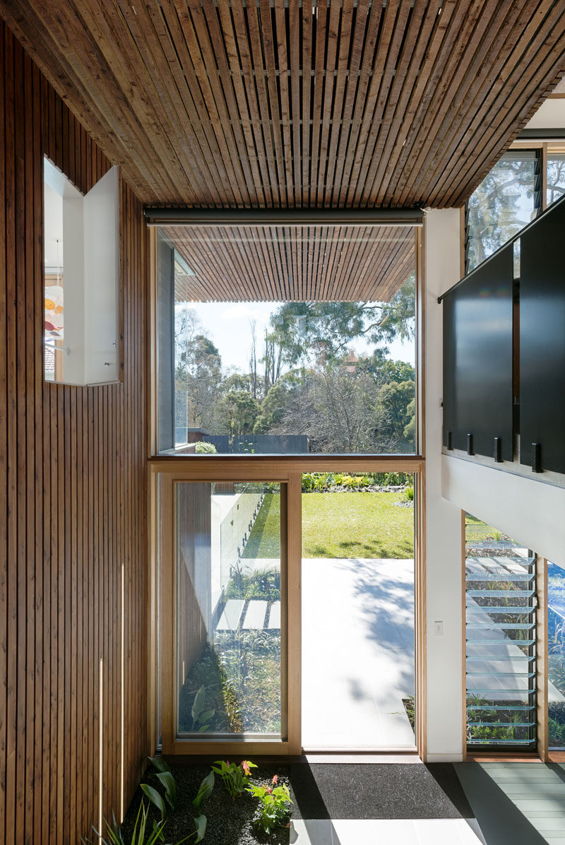 Entering from the back of this modern house, you can see how the wood strips continue from the outside of the house through to the interior, creating design continuity between inside and out. You can also see how large windows take advantage of the landscape outside and use the natural light to brighten the home.