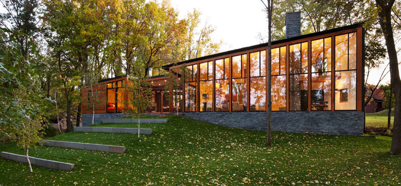 This modern house covered in wood, metal and stone, has floor-to-ceiling windows that follow the line of the roof to take advantage of the lakeside views and let in as much natural light as possible.
