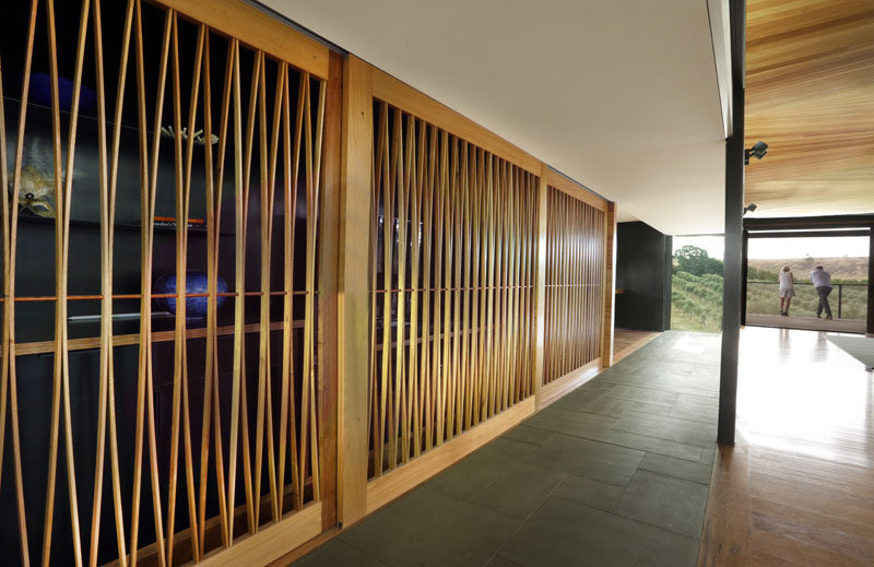 In this modern house, an artistic wood sliding door creates a screen that partially conceals an art collection confined to a small nook as well as a bar area.