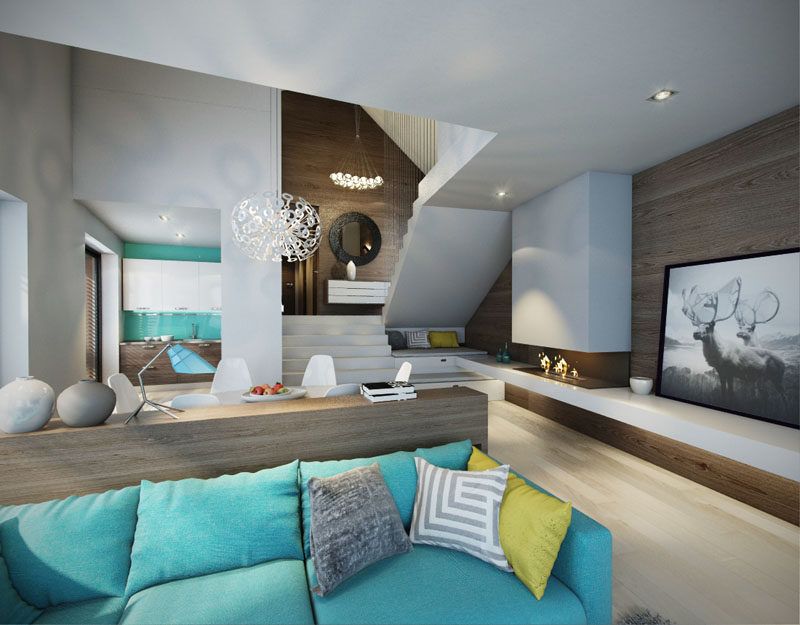 In this modern open plan interior, a turquoise couch matches the pop of blue in the kitchen and breaks up the mostly white and wood interior.