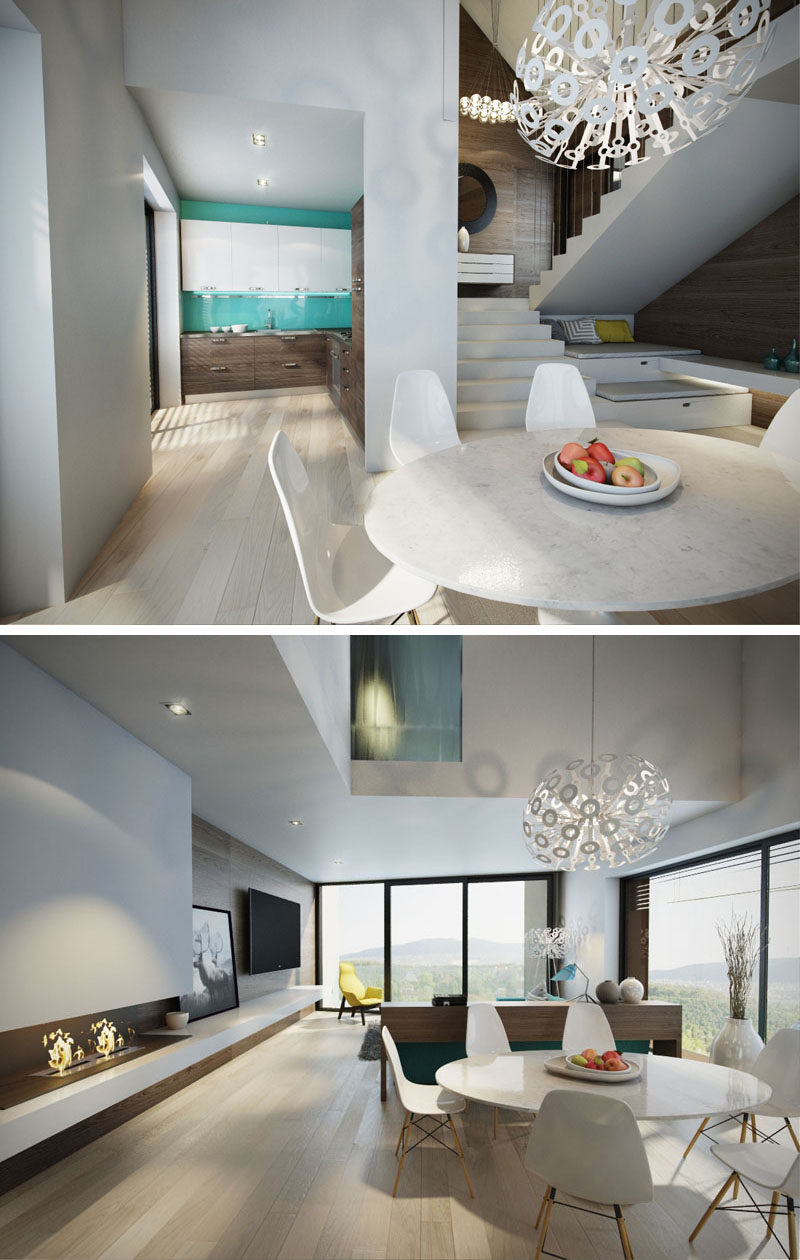 Stepping down from the entryway in this modern house, you enter the main dining and living area. The dining room has a small kitchen located behind it, a double-height ceiling void above is, and to the right and under the stairs, is a small nook for relaxing as well as a fireplace.