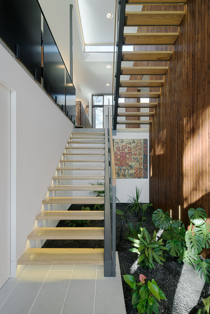 Light wood and steel stairs with hidden lighting underneath each tread creates a safe staircase that leads up to the main level of the home, and below the stairs is a small interior garden.