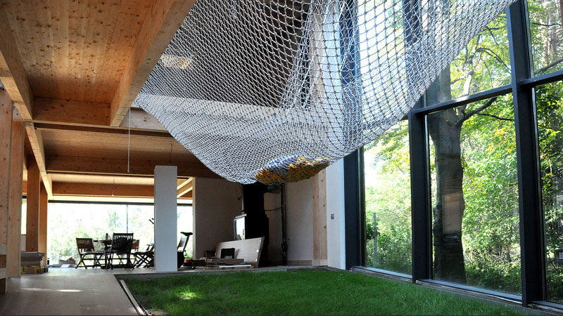 The large net in this home allows loungers to feel like they're actually hanging outside in a hammock thanks to the floor to ceiling windows on one side and the patch of real grass underneath.