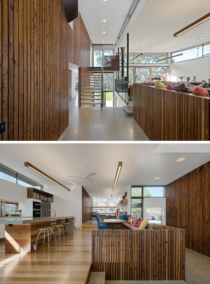In this modern house, dark wood paneling has been used on the walls and on some of the kitchen shelving while white walls reflect the light coming in through the many windows on the floor.