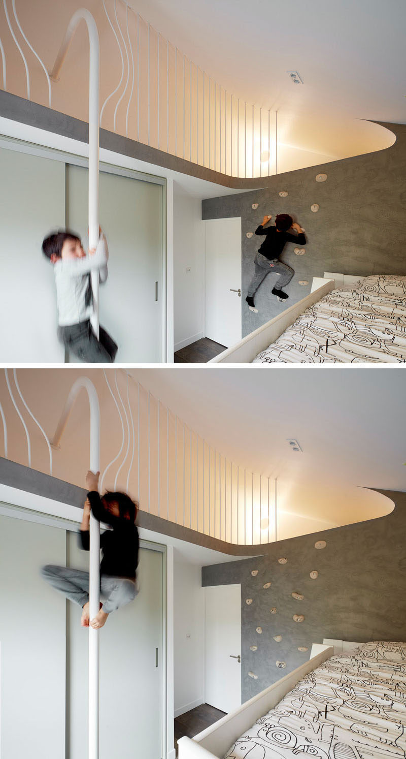 In this kids bedroom, a rock climbing wall lets the children climb up to a lofted area where they can slide down a pole to get down.