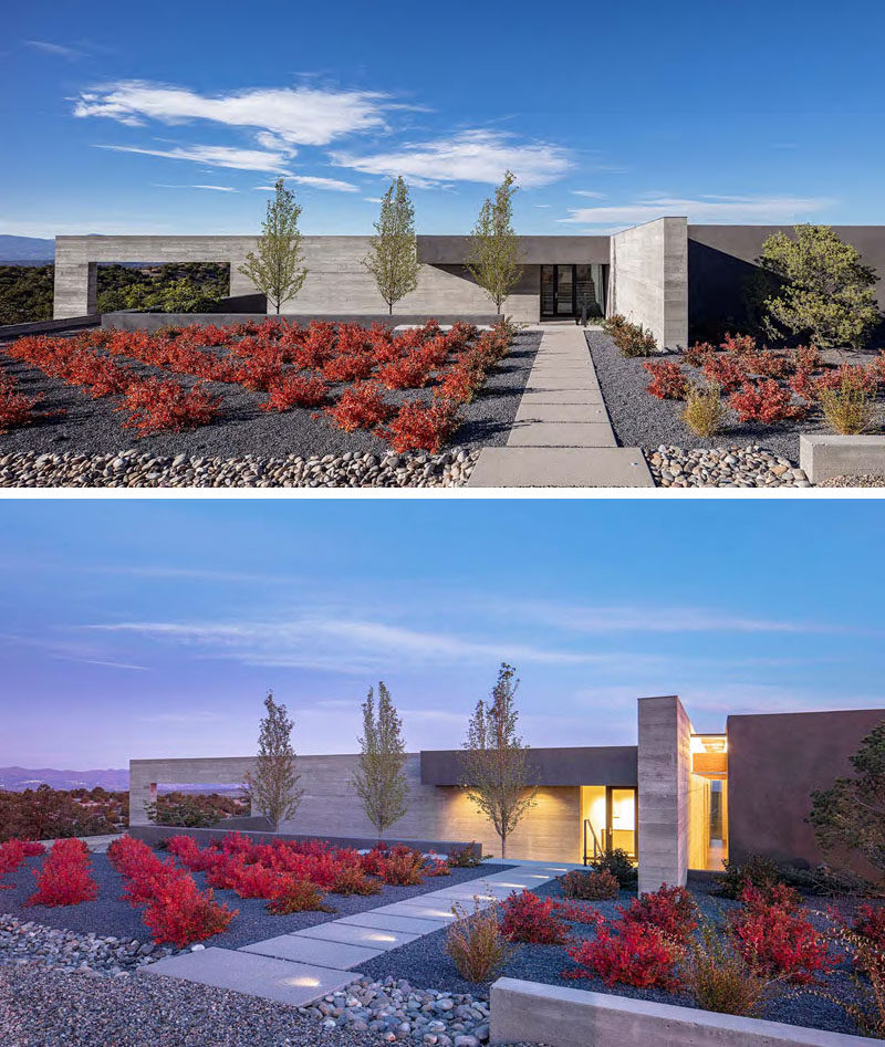 The curb appeal of this modern house features rows of colorful plants and dark gravel, that help to making the path to the front door stand out.