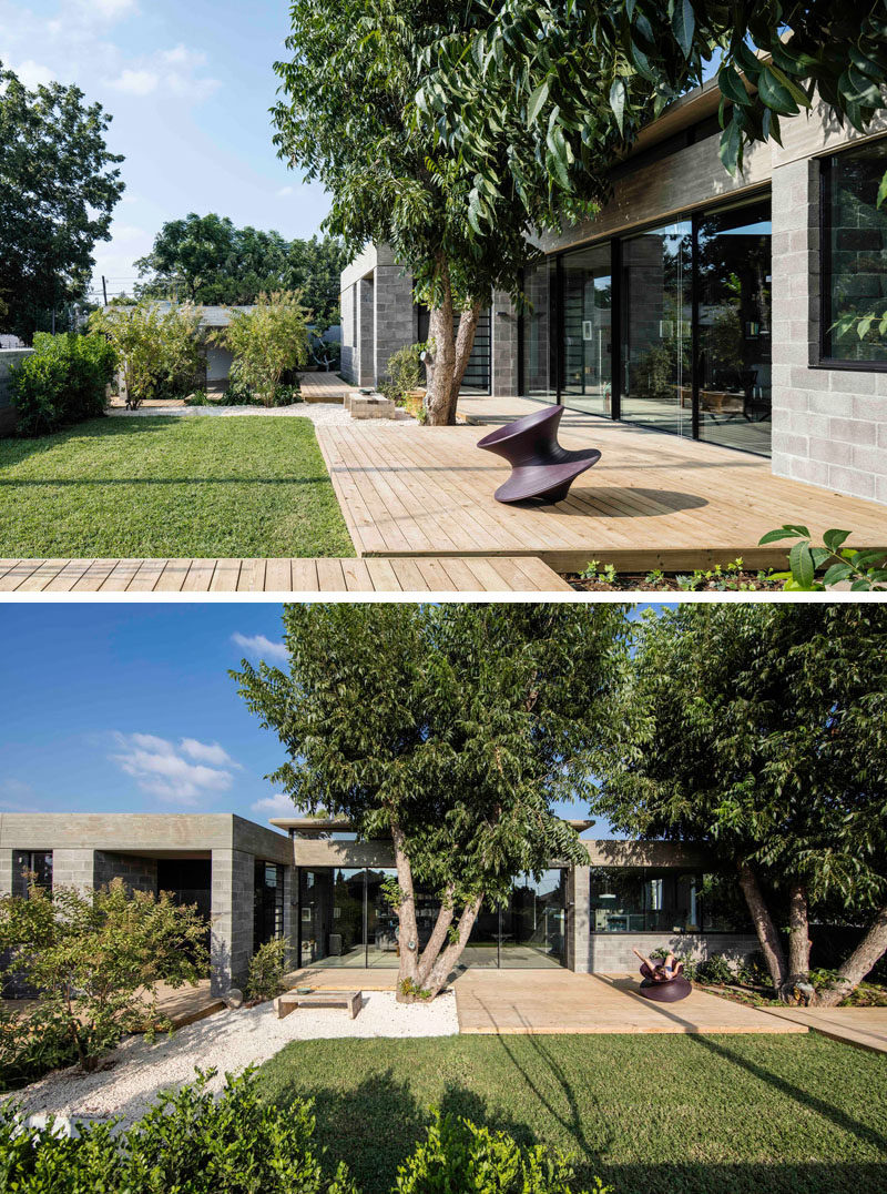 This modern house has a yard at the front of the house with a wood patio and a grassy lawn to give the children space to play.