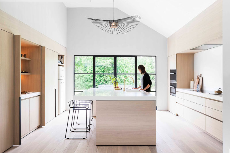 White Kitchen Lighting Light wood and white countertops create a neutral softness in this this modern and minimalist light wood and white kitchen features black accents like stools and window workwithnaturefo