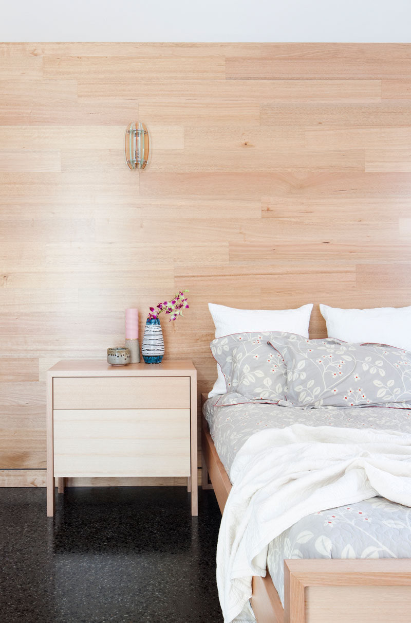 In this modern bedroom, light wood paneling lines the wall behind the bed and matches the bed frame and the night stand, creating a unified look, adding warmth, and keeping the room bright.