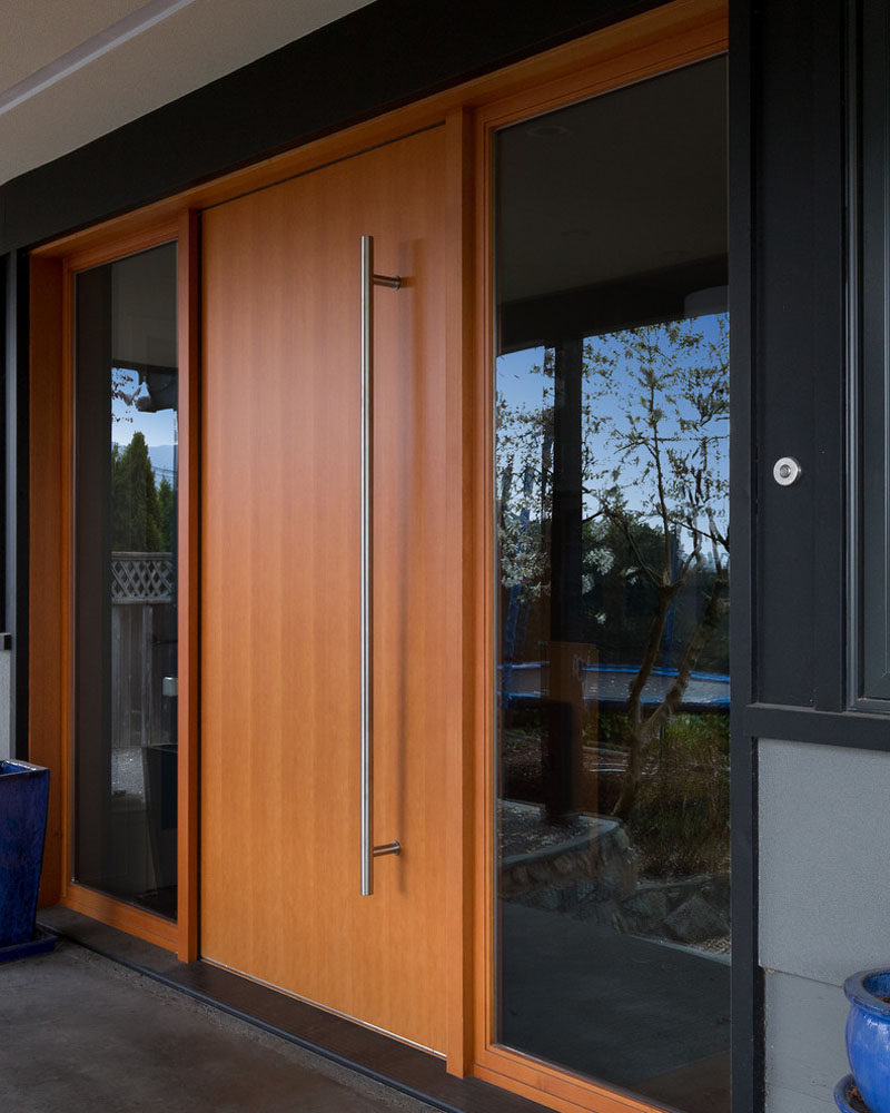 This light wood door features an oversized metal door handle and is flanked by windows on both sides to create a modern entry into this family home.