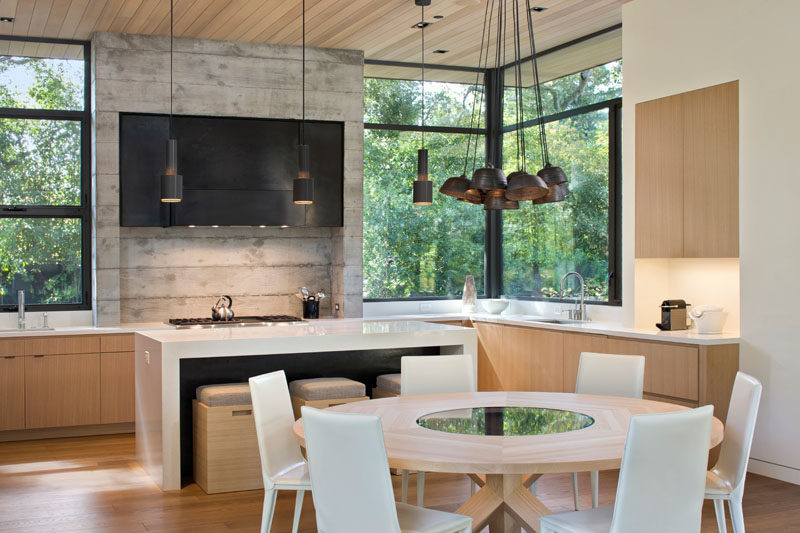 In this modern kitchen, the concrete and metal stove surround, wood cabinets, and white island and countertops create a modern look that's kept natural and bright thanks to the large windows looking out into the trees, and the pendant lights hanging above the island and dining table.