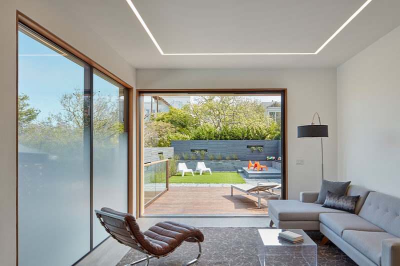 This modern house has a casual living area with partially opaque windows that provide privacy from the neighbors.