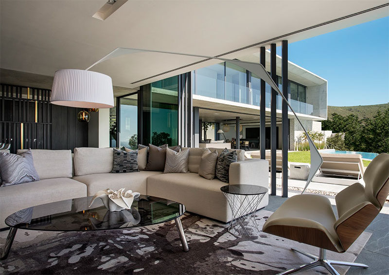 In this modern living room, sliding glass pocket doors open up to the backyard and swimming pool, and a comfortable L-shaped couch provides a place to watch a movie.