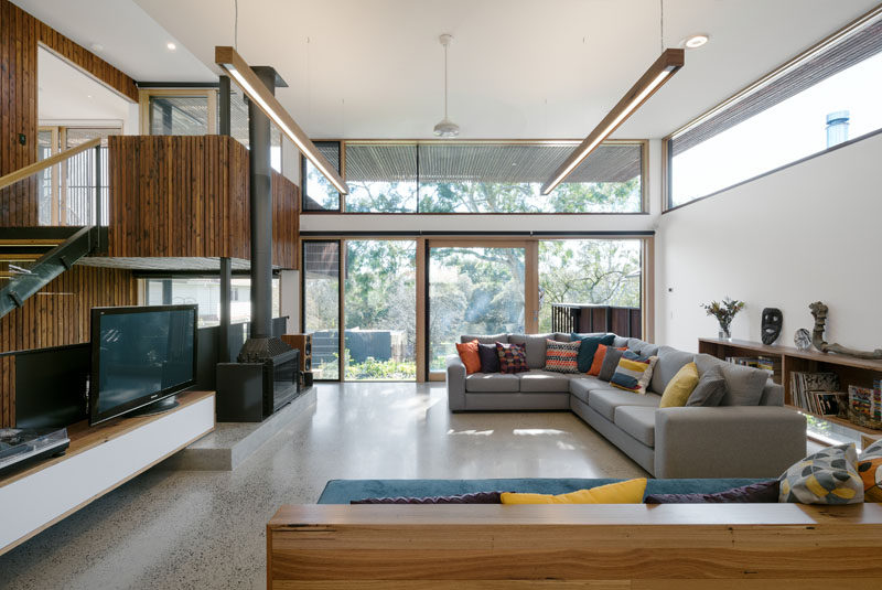 In the living room of this modern house, large windows look out onto the backyard and fill the room with natural light while the wood along the one side creates a cozy, warm, and natural feel in the space.