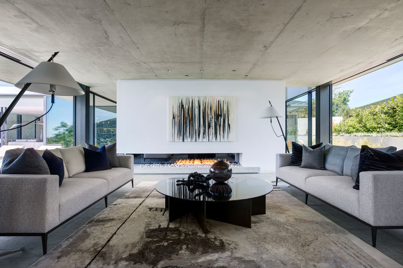 In this modern formal living room, large sliding glass doors can be opened to enjoy the breeze, and on a cooler night, a fireplace positioned within a white partition wall adds warmth.
