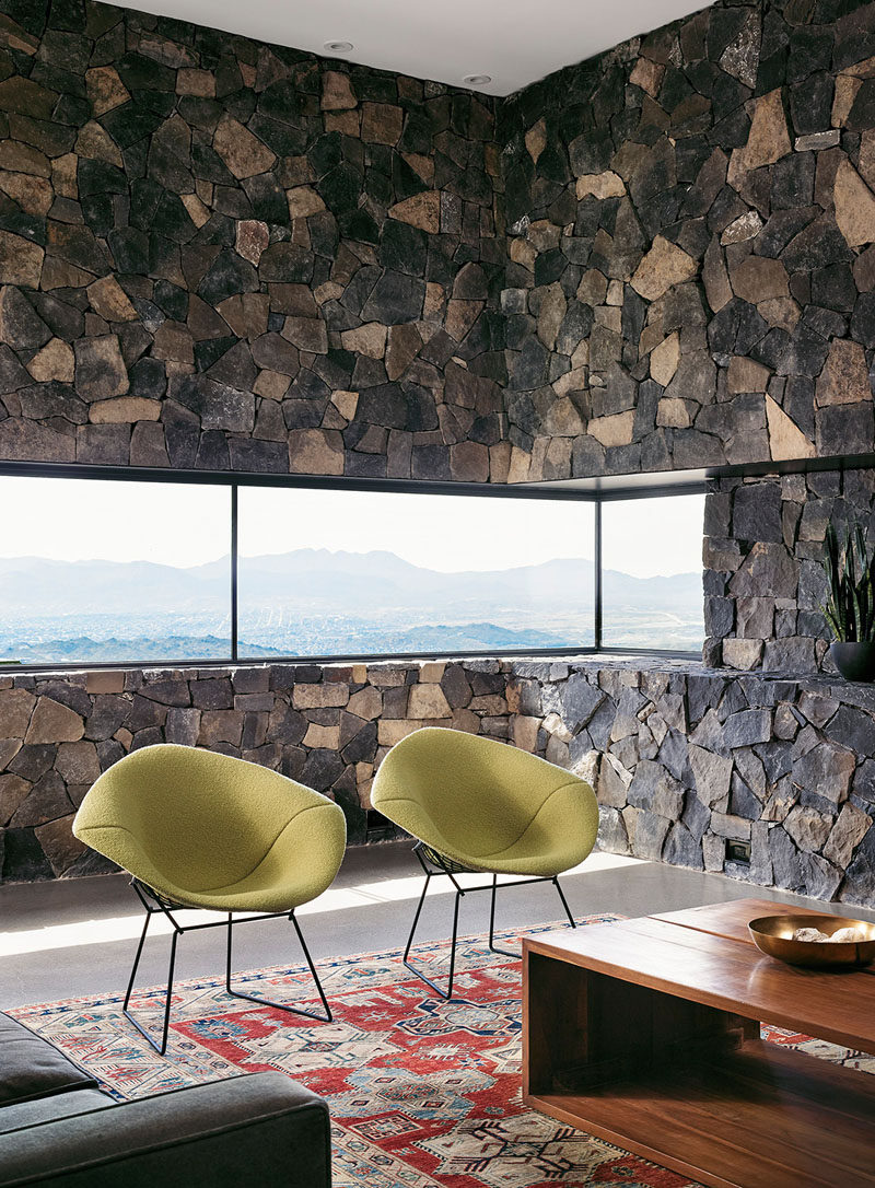 In the living room of this modern house, stone covers the walls and creates a rustic, mountain feel. A letter box window that wraps around the corner looks out to the valley and city below. Modern green chairs and a rectangular wood coffee table warm up the space and make it an inviting spot sit and watch the sunset.