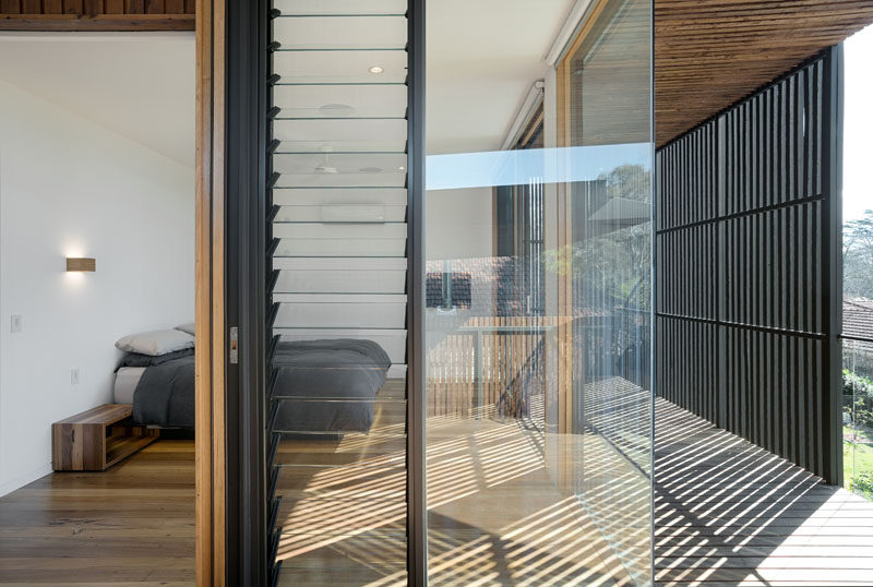 The master bedroom in this modern house is surrounded by windows that allow it take advantage of the landscape outside but also features a black privacy screen that prevents unwanted attention while in the bedroom.