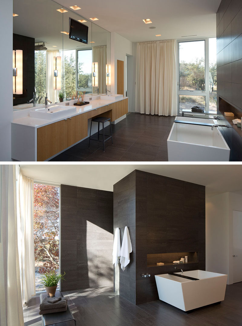 In this modern master bathroom, a floating double vanity with light wood cabinetry and white counters has a central cutout, just the right size for a stool and provides the perfect spot to sit and apply makeup. A stand alone tub is positioned against a partial wall covered with the same tiles as the floor. A built-in shelf in the wall next to the tub makes sure that everything you need while bathing is always within reach.