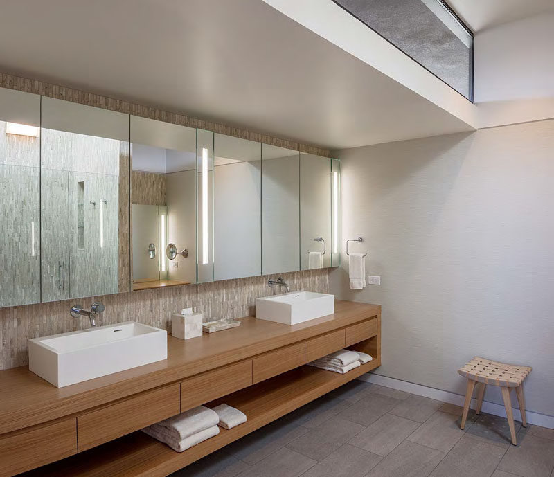 In this modern master bathroom, natural light from the clerestory window filters through to the space, while large mirrors fill the width of the wall. A floating wood double-sink vanity has plenty of drawer space and open storage.