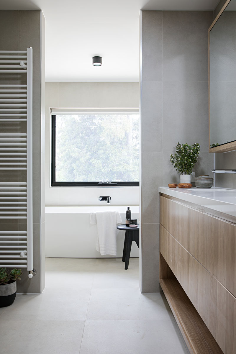 In this modern bathroom, a light wood vanity and plants add a natural touch to the grey and white bathroom.