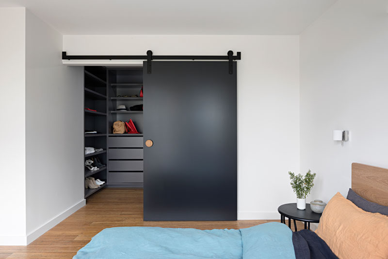 This modern master bedroom has a large walk-in closet hidden behind a matte black sliding barn door.