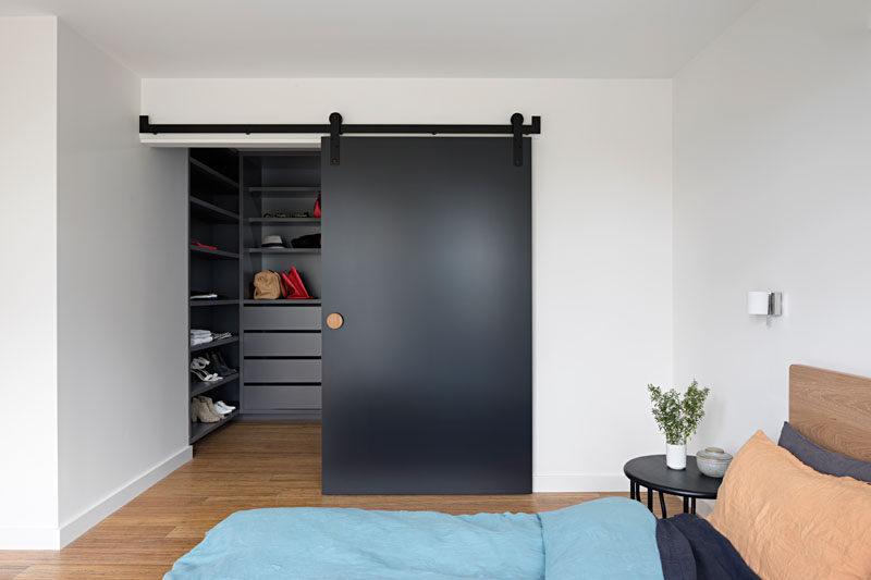 This modern master bedroom has a large walk-in closet hidden behind a matte black sliding barn door.