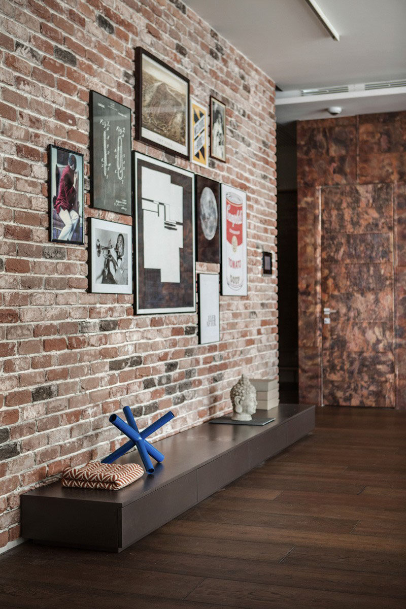 Artwork of various sizes have been hung on this exposed brick wall to add more life to the space, and the thin picture frames allow the pieces to stand out.