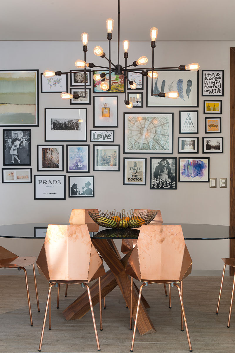 Prints and photos surrounded by simple black frames hang on the wall behind the dining table in this apartment and add color, personality, and life to the interior.