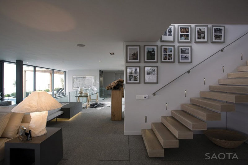 Photos in simple grey frames lead up the stairs of this home and create a simple gallery wall full of memories.