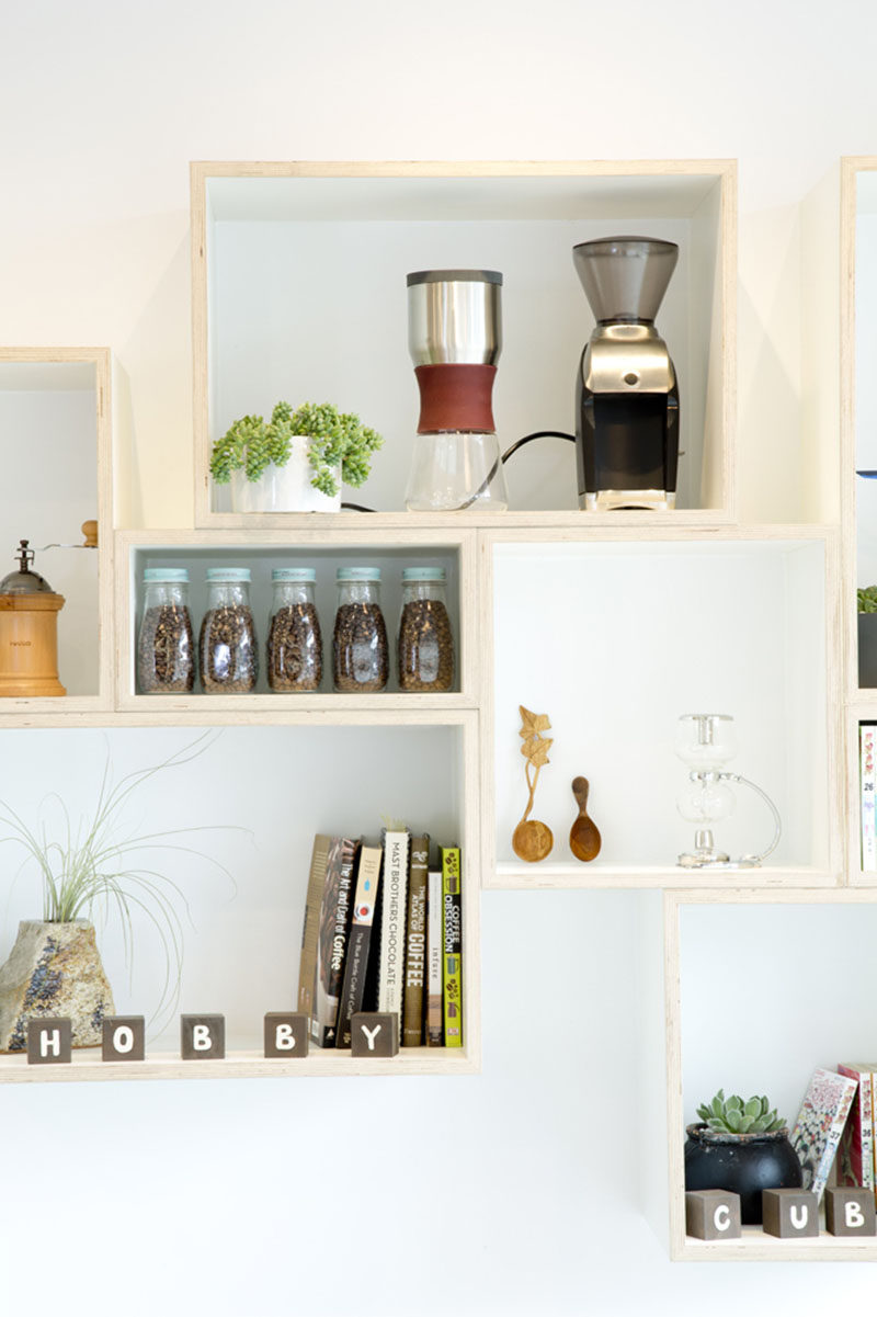 In this modern coffee shop design, there's a floating wood shelf made from rectangular boxes to display various items.